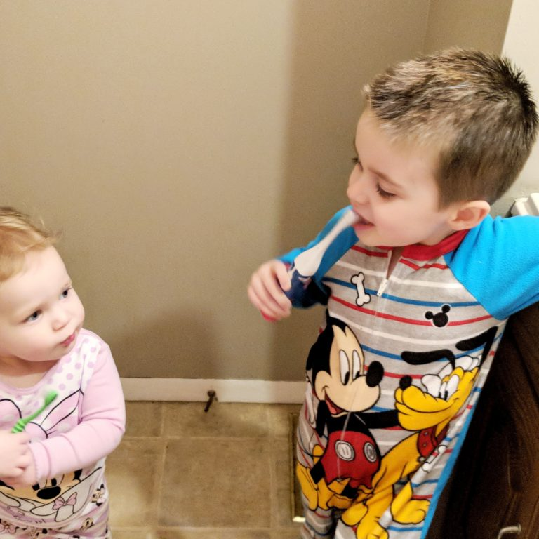 a toddler girl and preschool aged boy brushing their teeth in pajamas