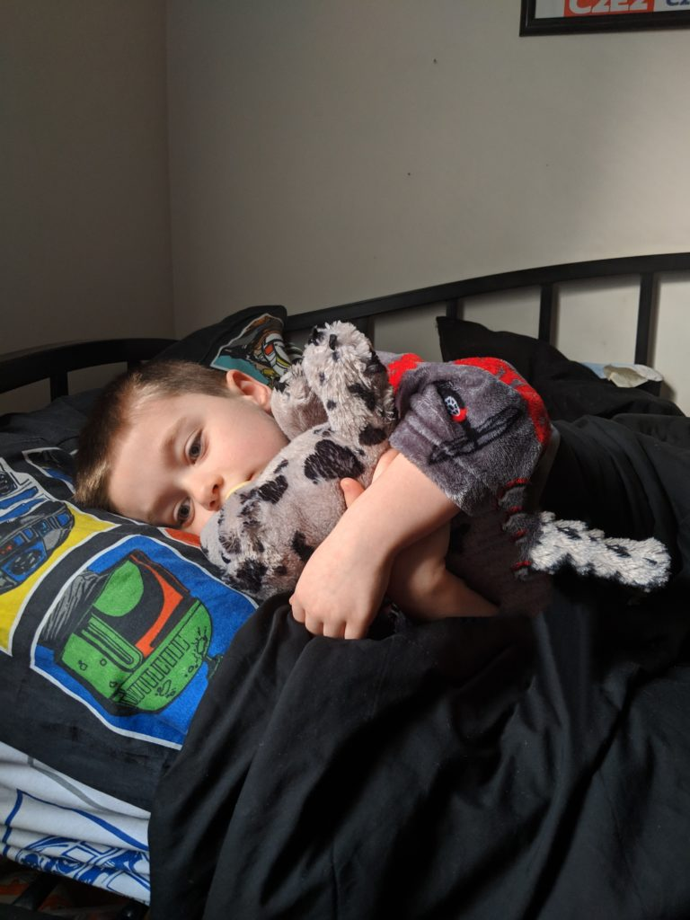 5 year old boy in grey robe lays in bed and hugs a stuffed seal