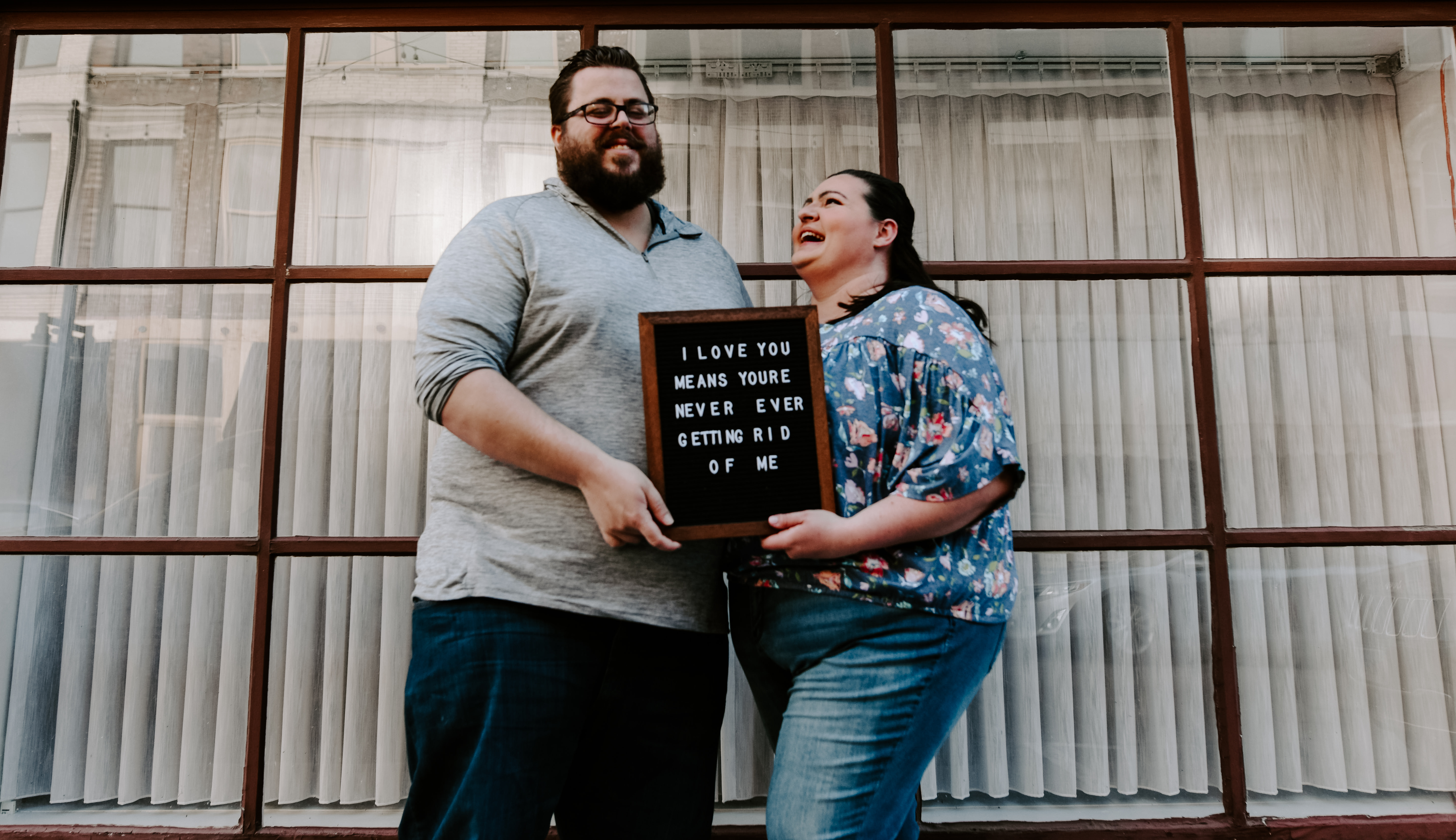 "laughing couple holds letter board that reads ""i love you means you're never ever getting rid of me"""