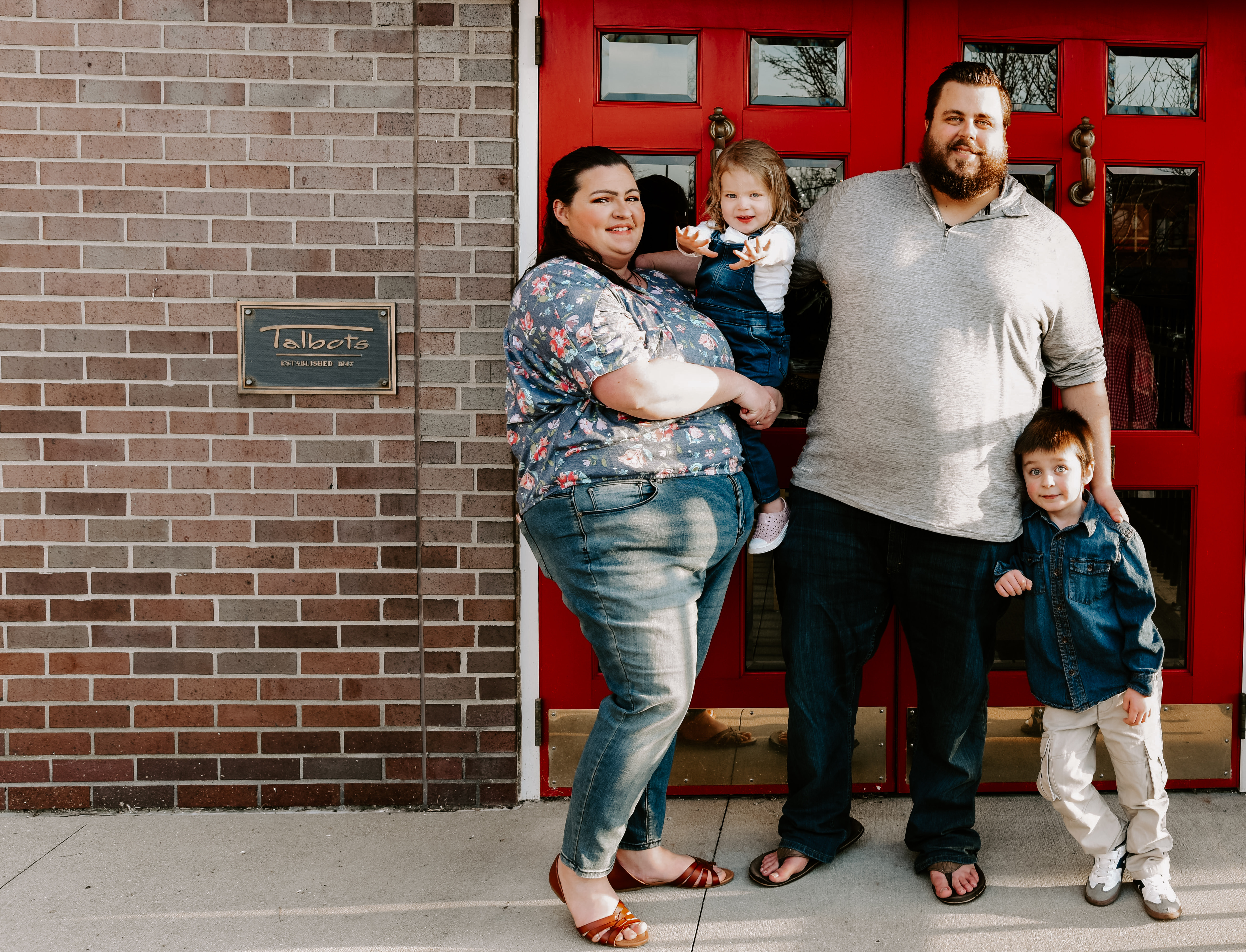 family of four smiles in front of bright red door