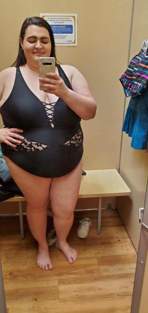 Aryn stands in front of a dressing room mirror and takes a selfie wearing a black one piece plus size swimsuit with lace cut outs on the hip