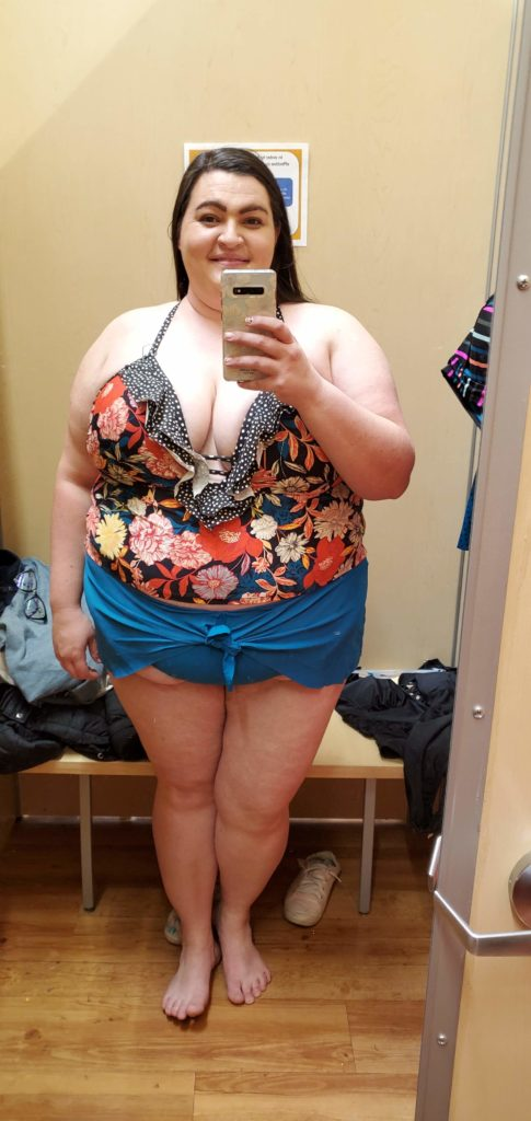 Aryn stands in front of a dressing room mirror and takes a selfie wearing a 2 piece plus size swimsuit with a floral top and blue tie front bottoms