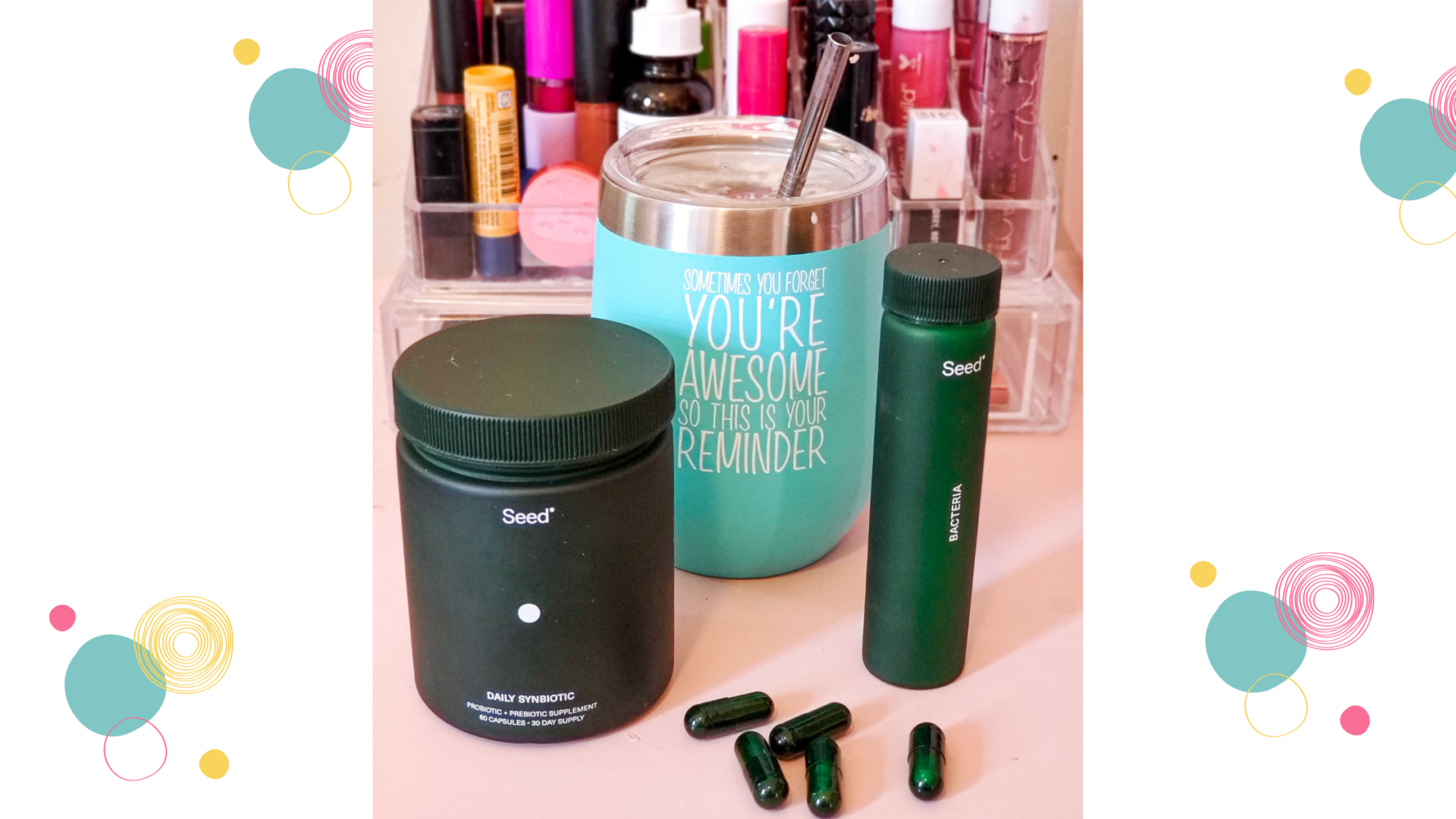 """Green Seed Probiotic containers sit on a pink cart in front of a tumber that reads """"Sometimes you forget you're awesome, so this is your reminder"""" and various makeup in an acrylic organizer."""