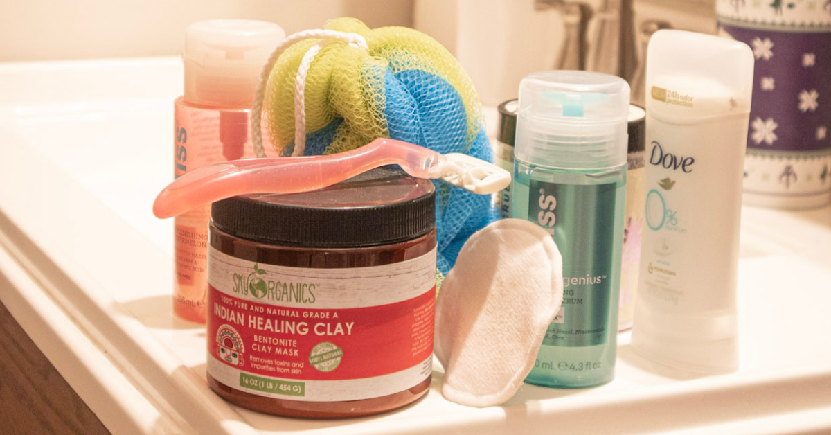 Various exfoliating products sit on a white bathroom sink